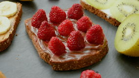 Sweet delicious toasts with raspberries, bananas and kiwi stock video footage