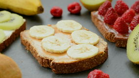 Sweet delicious toasts with ripe raspberries, bananas and kiwi stock video