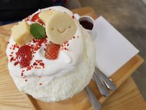 Smiley face on Bingsu. Sweet dessert Bingsu Kakigori topping with cheese cake, strawberry and smiley face cookie stock photography