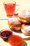 Sweet dessert: donuts with jam fillings and tea Royalty Free Stock Photo