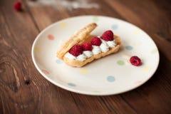 Sweet dessert with fresh raspberries on plate on wood table. Sweet dessert with fresh raspberries on plate on old wood table Royalty Free Stock Photo