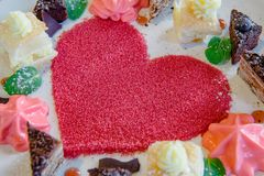 Sweet Dessert Heart In between small cakes. Composition of Sweet Dessert Sugar Heart In between small cakes Royalty Free Stock Images