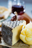 Sweet dessert liqueur wine in glass, hard cheeses Caciocavallo o. R Provolone, Tomme de Montagne, dried figs with figs bread, still life on wooden platter Royalty Free Stock Photo