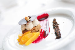 Sweet Dessert with nuts and mandarin. On strawberry jam and chocolate Stock Image