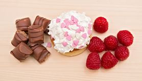 Sweet dessert Pancake with vanilla cream, raspberry and chocolate. Pancake with vanilla cream and whipped cream topping with small pink sugar hears. Red Stock Images