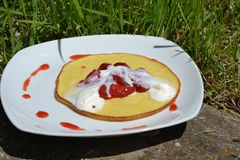 Sweet dessert - Pancakes with strawberries and cream on white plate Stock Photos