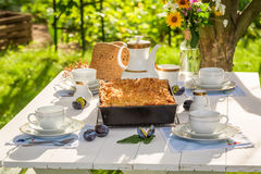 Sweet dessert with plum cake and coffee in the garden Stock Photography