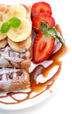 Sweet dessert:waffles with banana slices and strawberries and chocolate topping Stock Images