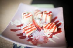 Sweet dessert wrapped in a roll of sushi rolls on a plate. Background royalty free stock photo