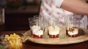 Sweet desserts in a cups at home. Sweet woman is making some interesting desserts in plastic cups. She is putting cut cake on the top of the cream stock video footage