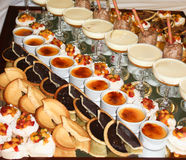 Sweet desserts including pavlova, chocolate mousse. Banquet table filled with assortment of sweet desserts including cakes, pavlova, creme caramel and chocolate Royalty Free Stock Photos