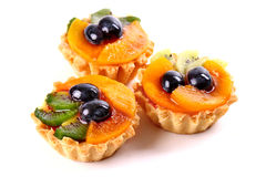 Sweet desserts with a kiwi, wine grapes and peaches Stock Photos