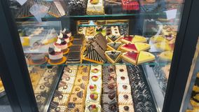 Sweet desserts at the shelves of the shop. Delicious colorful sweets at the shelf in the shop. Cupcakes, chocolate cakes, desserts at the transparent shelves stock footage