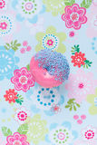 Sweet donut with pink icing, blue sprinkles against a floral bac Stock Image