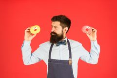 Sweet donut. Waiter in cafe. Doughnut calories. Glazed donut. Bearded well groomed man in apron selling donuts. Donut. Food. Baked goods. Sweets and cakes. Junk stock photography