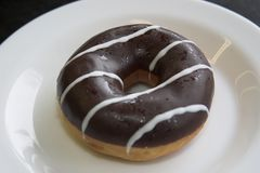 Sweet donute. Chocholate donut with nuts on white plate Stock Photo