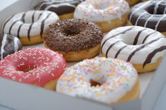 Sweet donuts. Assorted sweet donuts in a paper box royalty free stock photography