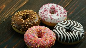 Sweet donuts with different glazing. From above assortment of tasty sweet donuts with different colorful glazing on wooden table stock images