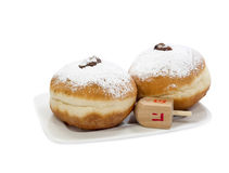 Sweet donuts for holiday of Hanukkah. Donuts (sufganiot) and dreidel are traditional Jewish attributes for holiday of Hanukkah Royalty Free Stock Images