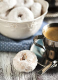 Sweet donuts with icing sugar and cup of coffee. On wooden table stock photos