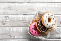Sweet donuts on an old wooden table, placed in a box, top view royalty free stock photography