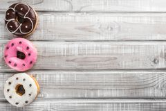 Sweet donuts on an old wooden table top view.  stock image