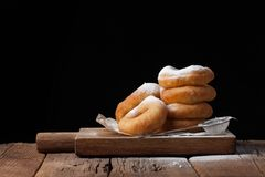 Sweet donuts with powdered sugar on a black background. Tasty, but harmful food on an old wooden table with copy space royalty free stock images