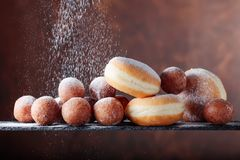 Sweet donuts powdered with sugar on a brown background. Sweet donuts powdered with sugar on a brown background, copy space royalty free stock image