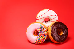 Sweet donuts on red. Background royalty free stock photography