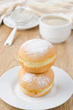 Sweet donuts sprinkled with powdered sugar and a cup of coffee Royalty Free Stock Images