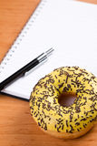 Sweet doughnut and spiral notebook Stock Photo