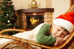 Sweet dream. Photo of cute infant wearing santa cap sleeping in rocking chair under blanket Royalty Free Stock Photos