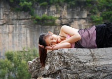 Sweet dream. An asian  girl lying on the stone and has a sweet dream Royalty Free Stock Photos
