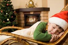 Sweet dream. Photo of cute infant wearing santa cap sleeping in rocking chair under blanket Stock Image