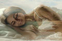Sweet dream. Double exposure of young attractive woman sleeping in bed and the beach. Sweet dream royalty free stock photos