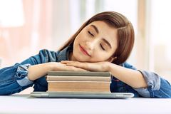 Cute teenage girl sleeping on a pile of books. Sweet dreams. Pleasant teenage girl sitting at the table and sleeping, with her head lying on the hands folded on Royalty Free Stock Image