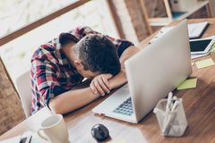 Sweet dreams at the work place. Sleepy tired freelancer is snoozing at wooden desk top, coffee cup and office stuff near, laptop royalty free stock photos
