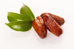 Sweet dried dates fruit on green leaf, mediterranean desert isol. Ated over white Royalty Free Stock Photography