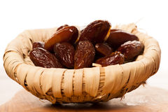 Sweet dried dates fruit in small bowl, mediterranean desert on w Royalty Free Stock Photo