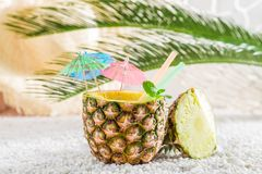 Sweet drink in pineapple with cocktail umbrellas. On white pebbles royalty free stock photography