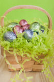 Easter chocolate eggs in a basket. Sweet Easter egg hunt treasure: basket filled with chocolate eggs in colorful wrapping royalty free stock images
