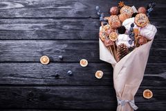 Sweet eatable bouquet wrapped in paper on black background. Sweet eatable bouquet wrapped in paper on black wooden background Royalty Free Stock Photos