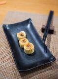 Sweet egg rolled is on black plate stock photography