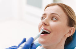 Sweet emotional woman sitting in dentists chair. Mastering the shiny smile. Attractive classy cheerful lady paying a regular visit for checkup and needing some royalty free stock image