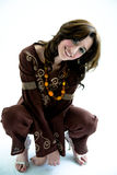 Sweet ethnic dress girl squat. Happy smiling woman in a ethnic brown top and pants squating on the floor Stock Image