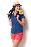 Sweet and extremely big. Young beautiful woman in funky hat holding a big lollipop and keeping mouth open while standing against white background Royalty Free Stock Images