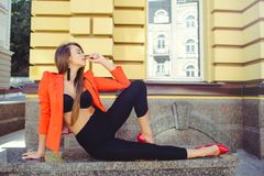 A sweet face is a mystery. Fashion portrait of a happy woman in red style jacket and black pants sits on the background of new hou. Ses, a new building. place royalty free stock photos