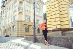 A sweet face is a mystery. Fashion portrait of a happy woman in a red style jacket and black trousers and a bra on the background. Of new houses, a new building stock images