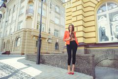 A sweet face is a mystery. Fashion portrait of a happy woman in a red style jacket and black trousers and a bra on the background. Of new houses, a new building stock image