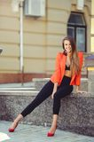A sweet face is a mystery. Fashion portrait of a happy woman in a red style jacket and black trousers and a bra on the background. Of new houses, a new building stock photography